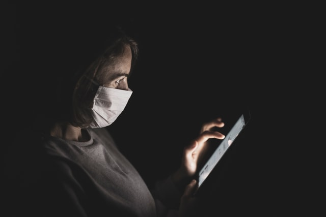 Woman working on ipad with a face mask